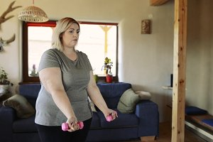 Attractive overweight woman at home working her biceps with dumbbells.