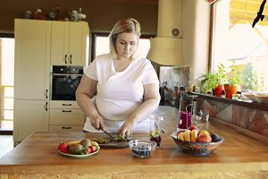 Attractive overweight woman preparing healthy smoothie.