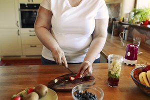 Unrecognizable overweight woman preparing healthy smoothie.