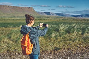 Cheerful woman photographing on nature