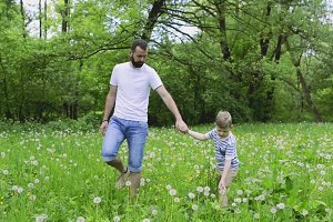Young father with little boy in nature, sunny spring day.