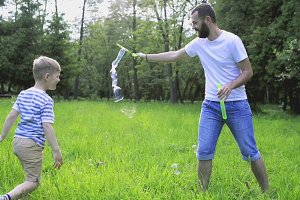 Hipster father and son blowing bubbles outdoors in park.
