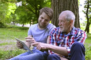 Young man and his senior father with tablet outdoors.