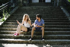 Young couple with smartphones sitting on stairs in town arguing.