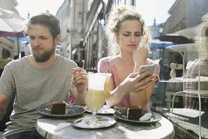 Young couple with smartphones sitting in cafe.