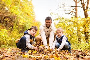 Young father with his sons in autumn forest.