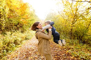 Beautiful young mother with her son in autumn forest.