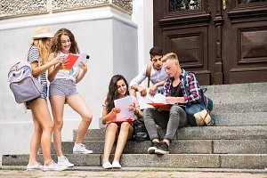 Teenage students sitting on stone steps in front of university.