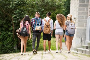 Group of attractive teenage students walking from university.