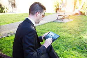 businessman with tablet in the park