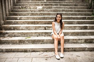 Beautiful teenage student girl sitting on stone steps.