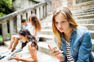 Teenage student girl with smart phone sitting on stone steps.