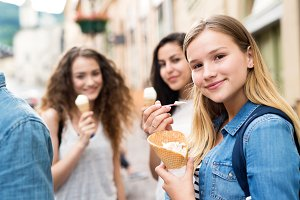 Attractive teenage students in town eating ice cream.