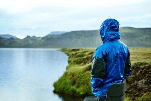 man on the Lake coast with mountain reflection, Iceland