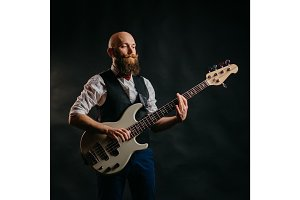 bearded man playing the guitar on a black background