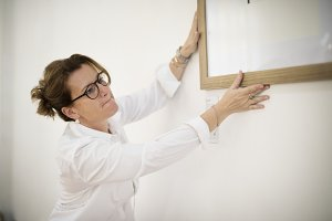 Woman hanging a frame on a wall