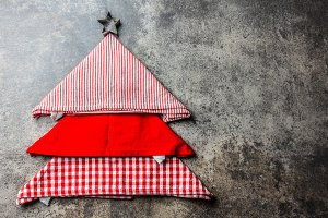 Christmas xmas food background with copy space. Christmas tree made from kitchen napkins and cookies star. Gray stone ackground. Holiday menu or cooking concept