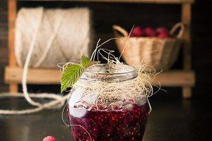 Ripe raspberries and jar of jam