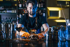 Barman is making cocktail at night club.