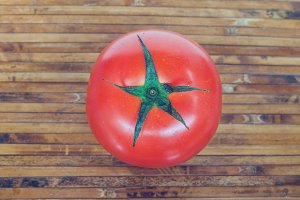Red tomato on bamboo plate