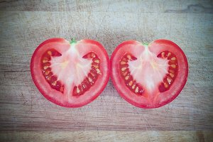 Half cut of red tomato in heart shap