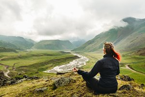 Young woman sits with her back on the top of a hill in a lotus pose and meditates against the backdrop of a picturesque valley and mountains in summer outdoor