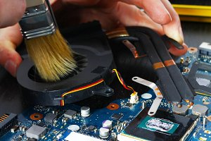 Notebook cooling system cleaning with a brush during service maintenance.