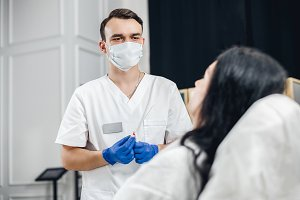 Male doctor in a mask conducts a diagnosis of the patients treatment.