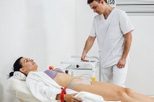 Male doctor with electrocardiogram equipment making cardiogram test