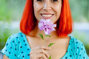Redhead woman with a pink flower