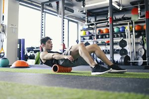 Young fit man in gym doing exercise with foam roller.