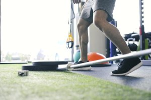 Unrecognizable fit man in gym preparing barbell for lifting
