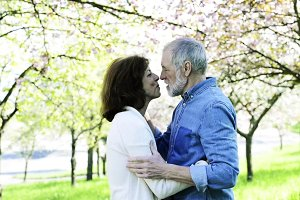 Beautiful senior couple in love outside in spring nature kissing.