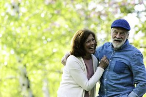Beautiful senior couple in love outside in spring nature lauging.