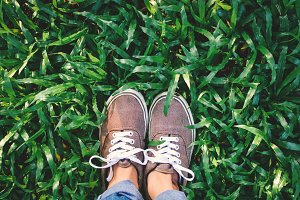 hipster feet girl on green grass