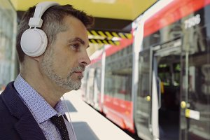 Handsome mature businessman waiting for tram, listening music.