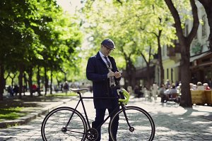 Mature businessman with smartphone and bicycle in the city.