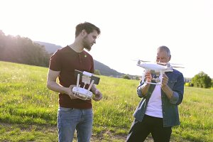 Senior father and his son with drone outdoors.