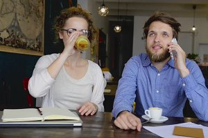 Two young designers on a meeting in cafe.