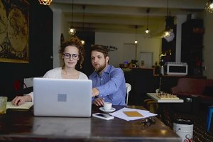 Two young designers with laptop working in cafe.