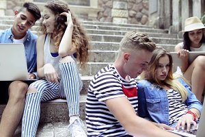 Teenage students with gadgets outside on stone steps.