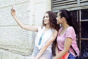 student girls in front of university taking selfie.