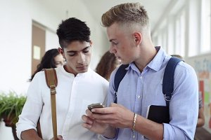 Teenage boys with a smartphone in a high school.