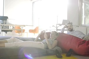 Business people in the office lying on bean bags with smart phones.