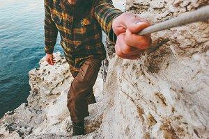 Man traveler climbing holding rope