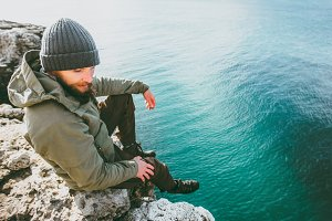 Bearded Man relaxing on rocky cliff