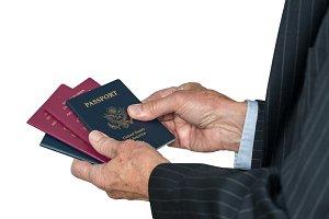 Senior caucasian hand choosing which passport to use