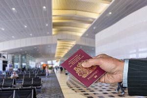 Senior executive arm holding UK Passport at airport terminal