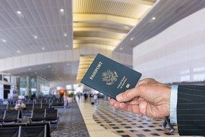 Senior executive arm holding US Passport at airport terminal