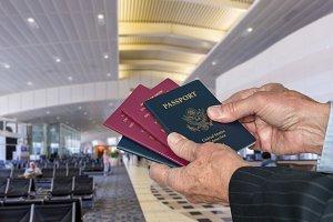 Senior executive arm choosing a passport at airport terminal